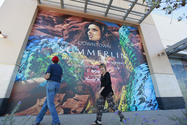Area residents Dino Fiorello, left, and wife Jenny walk by a large ad as work goes on the day before the official opening of Downtown Summerlin in Las Vegas on Wednesday, Oct. 8, 2014. (Chase Stev ...