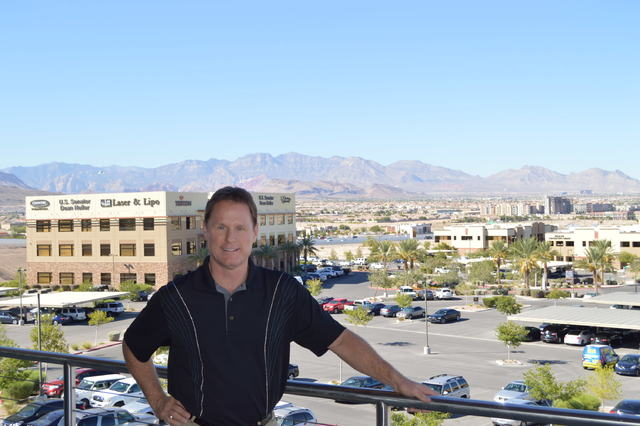 Lance Bradford co-founder of L.L. Bradford & Co. and CEO of Stable Development, stands on the balcony of his office building with another of Stable Development's buildings in the background. (Step ...