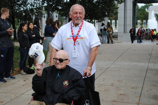 Glen Margerum, 90, of Henderson, tips his hat to the George Washington University volleyball players who lined the entrance of the WWII Monument to greet Honor Flight participants. Margerum was an ...