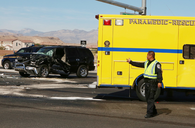 Las Vegas police officer directs traffic at the intersection of Blue Diamond Road and Durango Drive where a Clark County fire truck and an SUV collided on Friday, Oct. 31, 2014. Four people were t ...