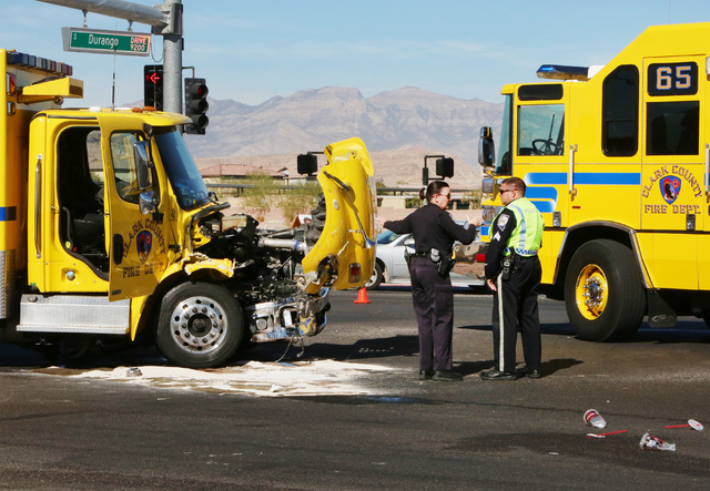 Las Vegas police officers are seen at the accident scene where a Clark County fire truck and an SUV collided at the intersection of Blue Diamond Road and Durango Drive on Friday, Oct. 31, 2014. Fo ...