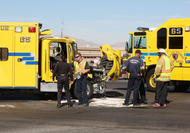 Clark County emergency workers stand at the accident scene where a Clark County fire truck and an SUV collided at the intersection of Blue Diamond Road and Durango Drive on Friday, Oct. 31, 2014.  ...