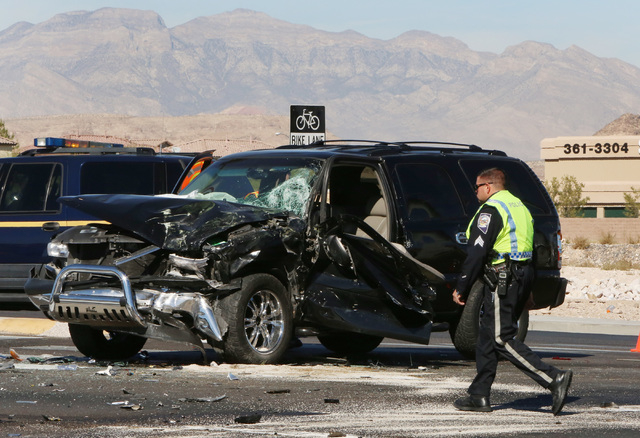 Las Vegas police officer walks past the accident scene where a Clark County fire truck and an SUV collided at the intersection of Blue Diamond Road and Durango Drive on Friday, Oct. 31, 2014. Four ...