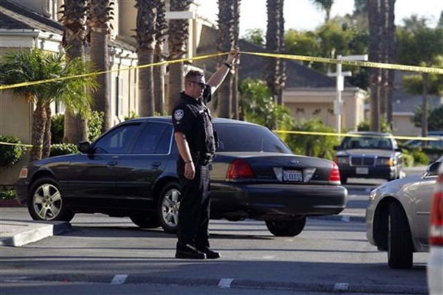 A police officer stands by the scene of a shooting in Bell Gardens, Calif., Tuesday, Sept. 30, 2014. (AP Photo/Nick Ut)