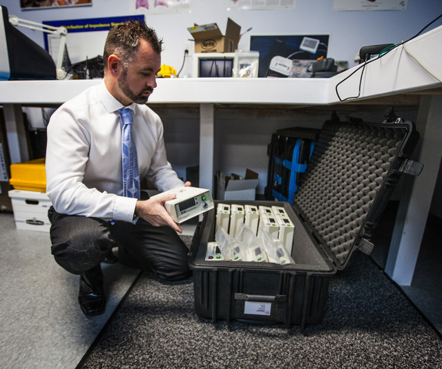 Dr. Mark O Grofa, chief technology officer for  Noninvasive Medical Technologies, packs  ZOE fluid status monitors at the company's office at 6412 S. Arville Street on Monday, Oct. 13, 2014.  The  ...