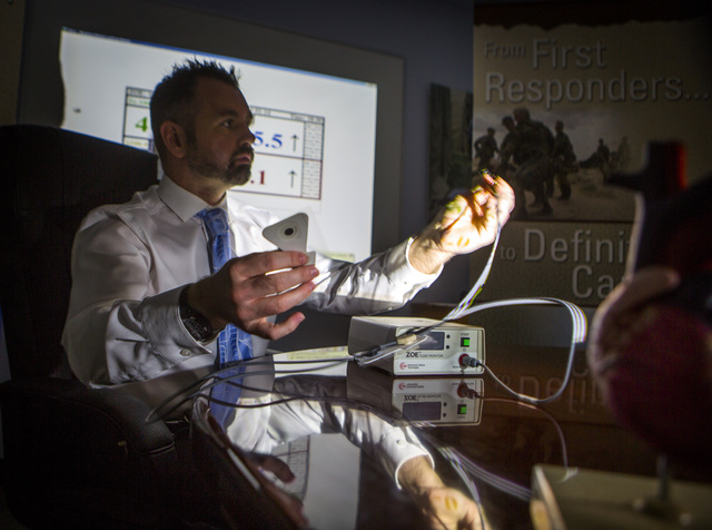Dr. Mark O Grofa, chief technology officer for  Noninvasive Medical Technologies, explains the ZOE fluid status monitor at the company's office at 6412 S. Arville Street on Monday, Oct. 13, 2014.  ...