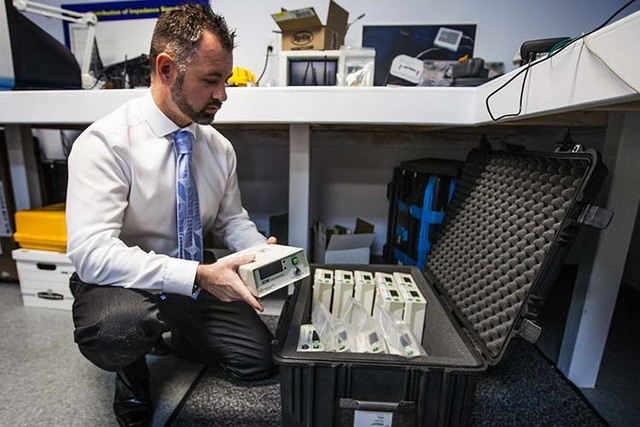 Dr. Mark O Grofa, chief technology officer for  Noninvasive Medical Technologies, boxes  ZOE fluid status monitors at the company's office at 6412 S. Arville Street on Monday, Oct. 13, 2014.  The  ...
