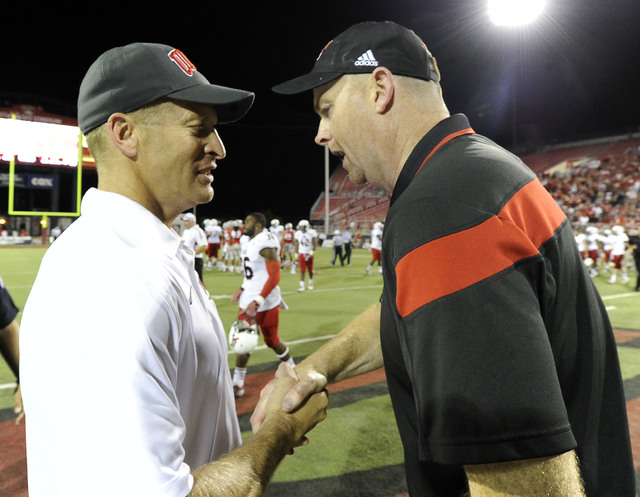 UNLV Rebels head coach Bobby Hauck, left, shakes hands with Northern Illinois Huskies head coach Rod Carey at the conclusion of their NCAA Football game at Sam Boyd Stadium in Las Vegas Saturday,  ...