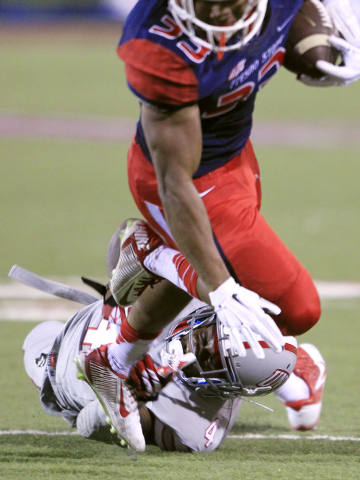 UNLV defensive back Sidney Hodge trips up Fresno State running back Marteze Waller during their game Friday, Oct. 10, 2014 at Sam Boyd Stadium. (Sam Morris/Las Vegas Review-Journal)