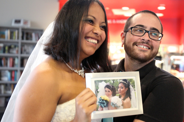 Alejandra, left, and Rhayemun Black pose with a photo of their commitment ceremony during a celebration after Nevada's same-sex marriage ban was lifted Tuesday, Oct. 7, 2014. The couple was able t ...