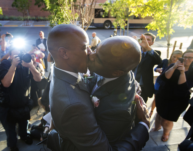 Sherwood Howard, left, and his husband Nevada Sen. Kelvin Atkinson, kiss after after gettingmarried on the steps of the Regional Justice Center on Thursday, Oct. 9, 2014.  They were the first same ...