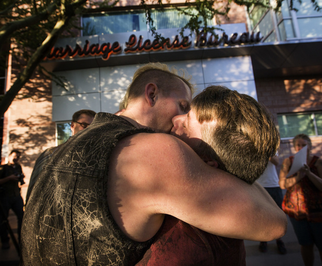 Dave Parry, left, and Morgan Ford kiss after getting married in front of the  County License Bureau  on Thursday, Oct. 9, 2014.  Today is the first for  same-sex couples to get married in Clark Co ...