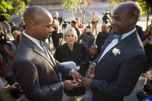 Sherwood Howard, left, places a ring on his husband, Nevada Sen. Kelvin Atkinson, during their wedding on the steps of the Regional Justice Center on Thursday, Oct. 9, 2014.  They were the first s ...