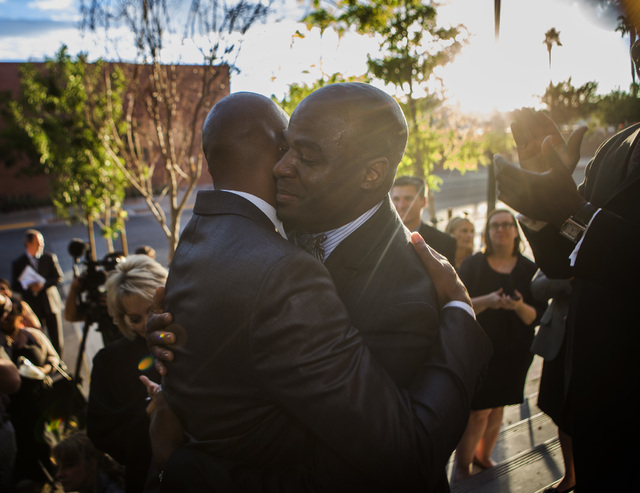 Sherwood Howard, left, and his husband Nevada Sen. Kelvin Atkinson, hug after  getting married on the steps of the Regional Justice Center on Thursday, Oct. 9, 2014.  They were the first same-sex  ...