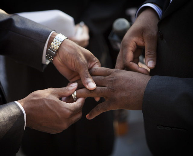 Sherwood Howard, left, places a ring his husband Nevada Sen. Kelvin Atkinson, during their wedding on the steps of the Regional Justice Center on Thursday, Oct. 9, 2014.  They were the first same- ...