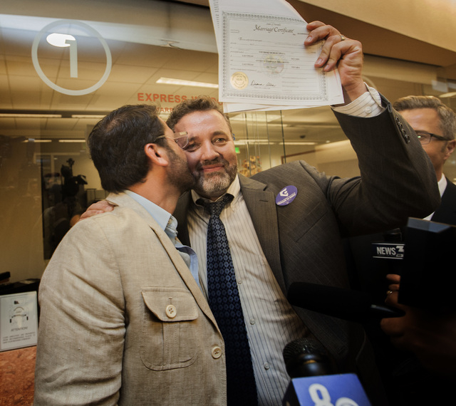 Antioco Carrillo, left and Theo Small celebrate after receiving the first same-sex license in Clark County on Thursday, Oct. 9, 2014at County License Bureau.  United States Federal Judge James C.  ...