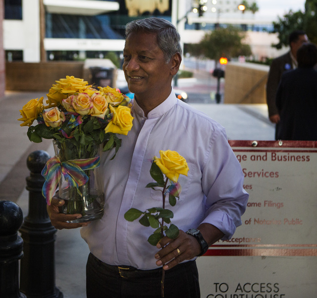 Reverend Ernie Martin  hands out flowers in front of the  County License Bureau on Thursday, Oct. 9, 2014.  Today is the first for  same-sex couples to get married in Clark County. (Jeff Scheid/La ...