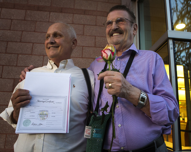 James Hook left, and Peter Schmitt hold their marriage license in front of the County License Bureau on Thursday, Oct. 9, 2014.  They have been together for 44 years. Today is the first for  same- ...