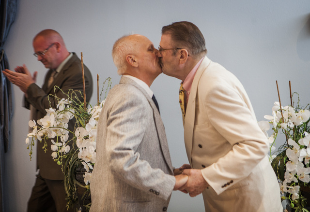 Rev. Jim McGinnis,left, claps after officiating the wedding for same-sex couple James Hook, 65, and Peter Schmitt,left, 74, kiss after getting married at Chapelle De L'Amour, 255 E. Bonneville Ave ...
