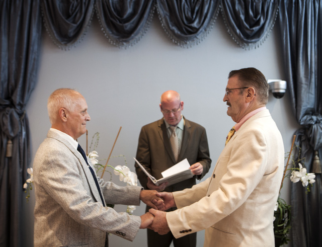 Rev. Jim McGinnis officiates the wedding for same-sex couple James Hook, 65, and Peter Schmitt,left, 74, kiss after getting married at Chapelle De L'Amour, 255 E. Bonneville Avenue on Friday, Oct. ...