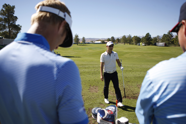 Sang-Moon Bae looks at his team during his driving range practice at TPC Summerlin, 1700 Village Center Circle, in Las Vegas Tuesday, Oct. 14, 2014. Bae is competing in the Shriners Hospitals for  ...