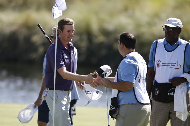 Webb Simpson shakes hands with his game assistants after completing his game on the 18th green during his Pro-Am round in the Shriners Hospitals for Children Open golf tournament at TPC Summerlin, ...