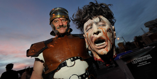 Dennis Laidlaw, as a gladiator, poses with his winning head, during the 5th annual Halloween parade along East Fremont Street in Las Vegas on Friday, Oct. 31, 2014. (David Becker/Las Vegas Review- ...