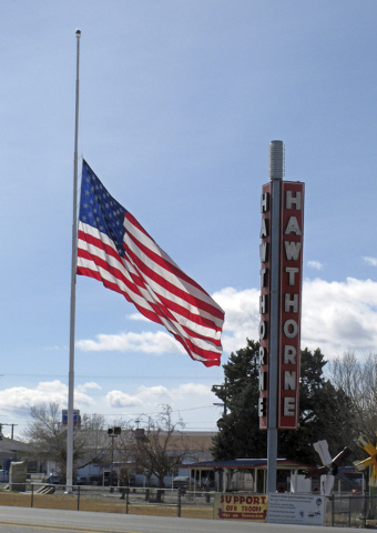 An American flag waves at half staff in the town of Hawthorne near the Hawthorne Army Depot on Tuesday, March 19, 2013, where seven Marines were killed and several others seriously injured in a tr ...