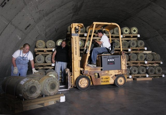 From left, Misty McNamara, Dennis Mathis and Dana Towe stack 750 pound bombs into a magazine at the Army Ammunition Depot in Hawthorne, Nev. Wednesday, May 25, 2005.  The depot is on the list of p ...
