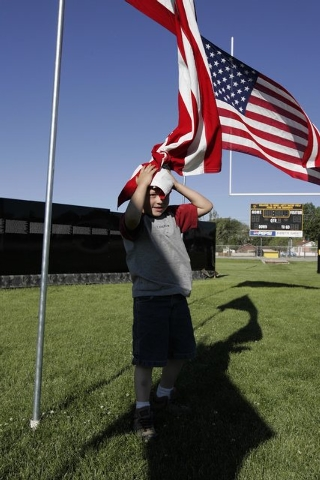 Five-year-old Bradley Sorensen plays with a flag at the traveling Vietnam Vets memorial wall in Hawthorne, Nev. Tuesday, May 24, 2005.  Hawthorne calls itself America's Patriotic Home. (John Loche ...