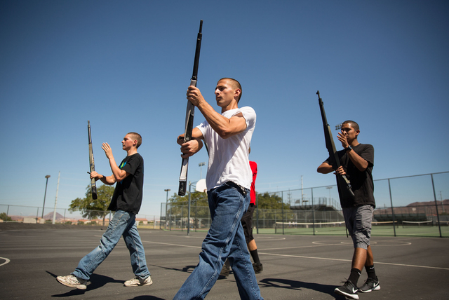 Basic High School Junior ROTC members James Werner, 16, left, Aaron Bates, 16, center, and Kenny Calzada, 17, right, practice their armed drill team program at the high school Friday, Sept. 19, 20 ...