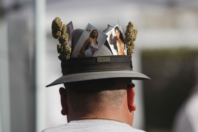 A man wears marijuana buds and phone sex advertising cards in his hat during the first annual Hemp Fest Saturday, Oct. 4, 2014 at the Clark County Government Center. (Sam Morris/Las Vegas Review-J ...