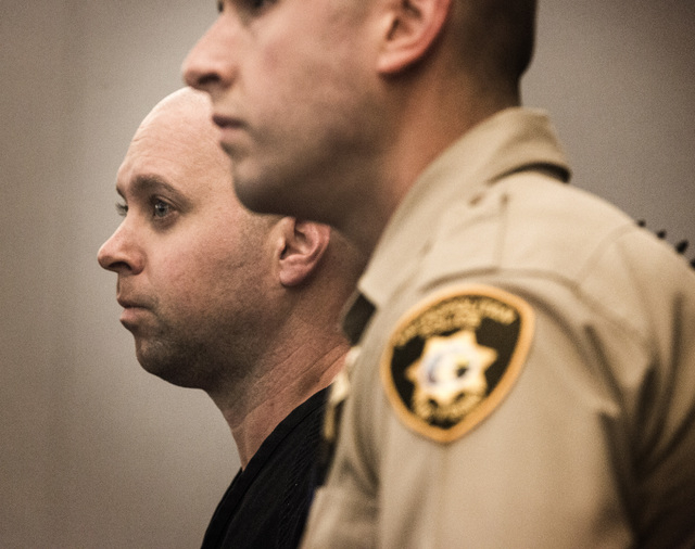Metro officer James Henry, 37, left,appears in Las Vegas Justice court on Friday, Oct. 24, 2014. He faces 10 counts each of possession of child pornography and distribution of child pornography. ( ...