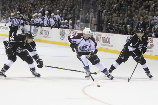 Colorado Avalanche left wing Alex Tanguay splits Los Angeles Kings defenseman Slava Voynov, left, and Drew Doughty during their pre-season game Saturday, Oct. 4, 2014 at the MGM Grand Garden Arena ...