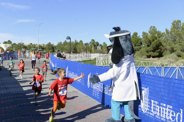 A participant gives Dr. Health E. Hound a high five near the finish line at the 2014 UnitedHealthcare IRONKIDS Las Vegas Fun Run at Henderson Pavilion, Saturday, Oct. 4, 2014. (Bryan Steffy/Specia ...