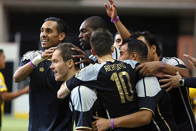 Las Vegas Legends' Boris Gujic, second from left, is swarmed by his teammates including Ivan Simental, far left, and Uzi Tayou, center back, after scoring a goal during a Major Arena Soccer League ...
