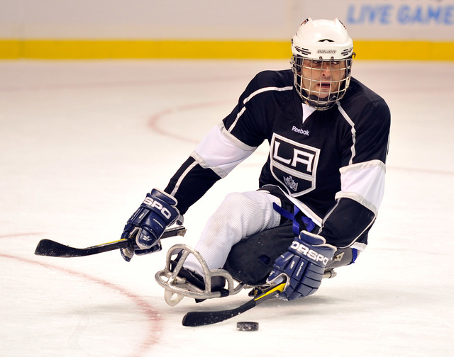 Los Angeles King Ahmad Karimzada of Las Vegas brings the puck up the ice during his sled hockey game against the Colorado Avalanche at the MGM Grand Garden Arena on Friday, Oct. 3, 2014. (David Be ...