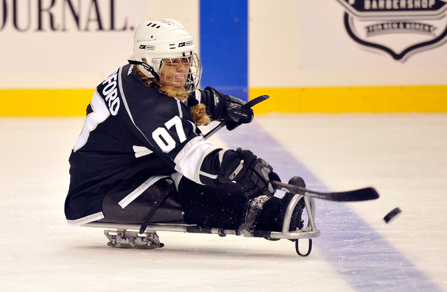 Los Angeles King Darlene Bradford hits the puck during her sled hockey game against the Colorado Avalanche at the MGM Grand Garden Arena on Friday, Oct. 3, 2014. (David Becker/Las Vegas Review-Jou ...