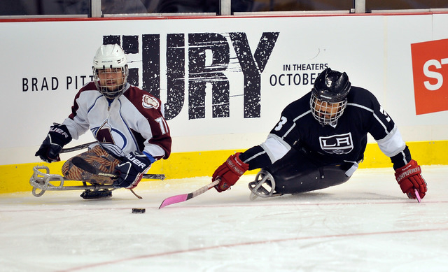 Los Angeles King Wesley Barnientos, right, reaches for the puck against Colorado Avalanche's Alexi Salamone during their sled hockey game at the MGM Grand Garden Arena on Friday, Oct. 3, 2014. (Da ...