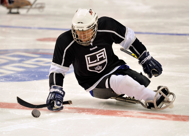 Los Angeles King Ahmad Karimzada of Las Vegas drives the puck up the ice during his sled hockey game against the Colorado Avalanche at the MGM Grand Garden Arena on Friday, Oct. 3, 2014. (David Be ...