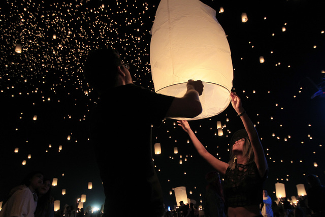 Justin Smith, from New York, and Trixie Encomienda, from Los Angeles, prepare to launch a paper lantern at the RiSE Festival Saturday, Oct. 18, 2014 on a dry lake bed near Jean.  (Sam Morris/Las V ...