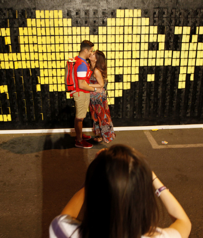Elizabeth Wong kisses William Rothwell while China Obenchain photographs them at the Life is Beautiful festival in downtown Las Vegas on Sunday, Oct. 26, 2014. (Justin Yurkanin/Las Vegas Review-Jo ...