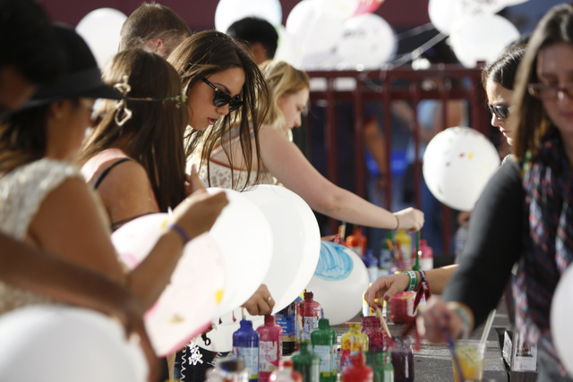 People decorate helium filled balloons with messages during day two of the Life Is Beautiful music and art festival in downtown Las Vegas Saturday, Oct. 25, 2014. (Erik Verduzco/Las Vegas Review-J ...