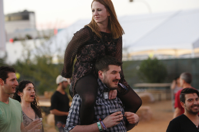 Nick Barlow carries his friend Kimberley Hyson during day two of the Life Is Beautiful music and art festival in downtown Las Vegas Saturday, Oct. 25, 2014. (Erik Verduzco/Las Vegas Review-Journal)
