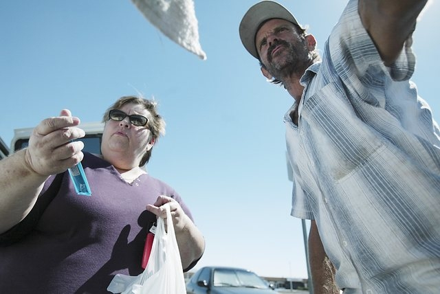 Homeless advocate Linda Lera-Randle El, left, holds a tube of peanut butter for Terry, a homeless man  who washes car windows for a living, as she makes a food delivery stop at Huntridge Circle Pa ...