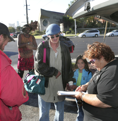 Homeless advocate Linda Lera-Randle El, right, founder and director of the Straight From the Streets charity, convinces Kevin LaSalle and his 7-year-old daughter Vanessa to attend the Homeless Sta ...