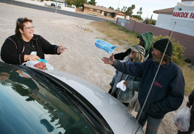 Straight from the Streets director Linda Lera-Randle El, left, tosses a knit cap to 45-year-old homeless man, Gregg Koltz, right, while they stand in a vacant lot off Lake Mead Boulevard in North  ...