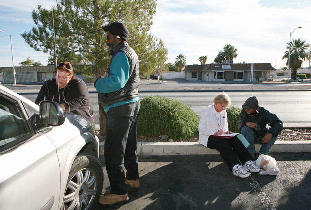 Straight from the Streets director Linda Lera-Randle El, left, issues a bus pass to a homeless man who calls himself Earl in a parking lot near Arizona Charlie's casino in Las Vegas Thursday, Nov. ...