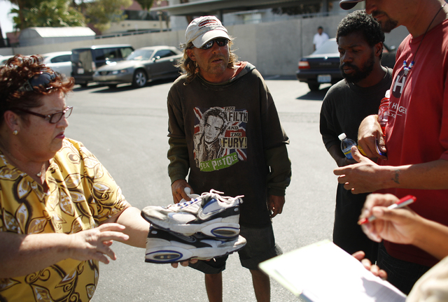 Linda Lera-Randle El, left, hands out clothing, food and bus passes to homeless men, continuing from left, Patrick Henry Hamilton, Michael Edwin and Jason Pinkoson on Thursday, July 30, 2009, in L ...