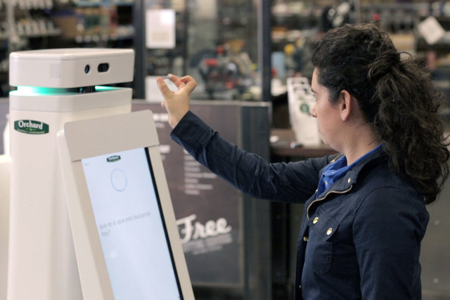 A woman holds a nail up to be scanned by an OSHbot robot. The robots are equipped with 3D cameras so they can scan and identify items. And customers can research items they want to buy on their sc ...